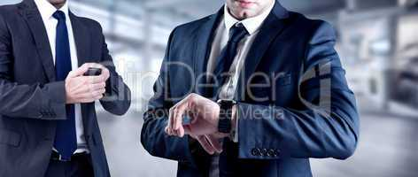Composite image of focused businessman texting on his mobile pho