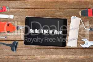 Build it your way against tools and tablet on wooden background