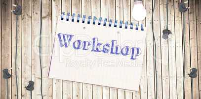 Workshop against notepad on wooden surface