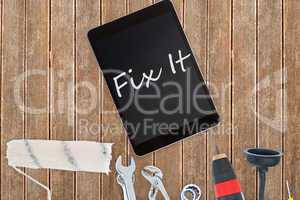 Fix it against tools and tablet on wooden background