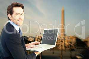 Composite image of smiling businessman using a laptop
