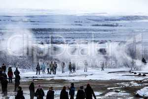 Visitors watching the eruption of a geyser in Iceland