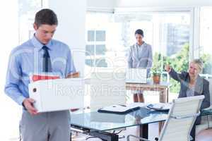Businesspeople carrying their belongings in box
