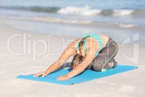 Fit woman stretching her back on exercise mat