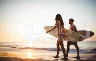 Couple holding surfboards looking at ocean