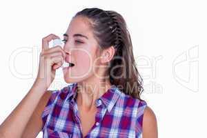 Pretty brunette woman using asthma inhaler