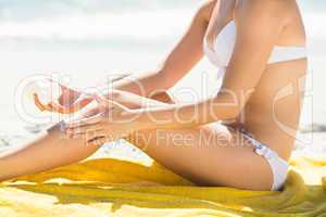 Close up view of Pretty blonde woman putting sun tan lotion on h