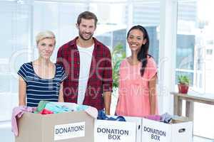Smiling young friends volunteers separating clothes