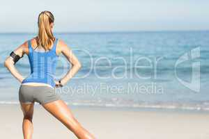 Wear view of fit woman stretching her leg