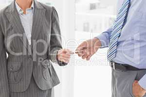 Businessman giving his business card to his colleague
