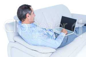 Smiling businessman lying on a sofa holding a laptop