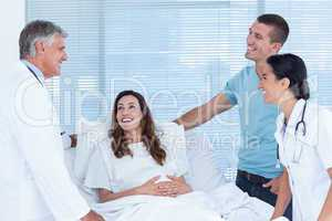 Future parents talking with smiling doctors