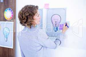 Wear view of creative businesswoman writing on post it