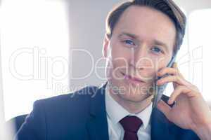 Confident businessman looking at camera while having a phone cal