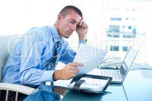Tired businessman looking at his laptop and his files