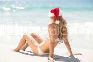 Wear view of blonde woman looking at the sea with santa claus ha