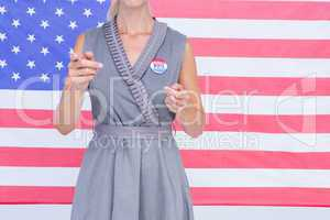 Blonde woman gesturing in front of american flag with badge