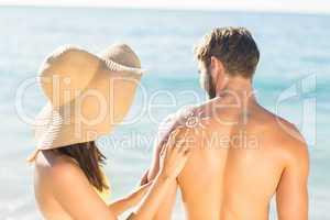 pretty brunette putting sun tan lotion on her boyfriend