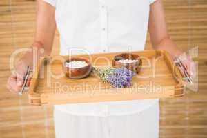 Therapist holding tray of beauty treatments