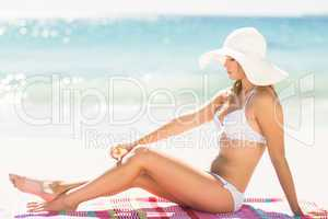 Pretty blonde woman putting sun tan lotion on her leg