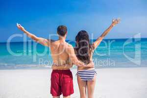 Rear view of happy couple with arms outstretched at the beach