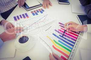 Business team analyzing bar chart graphs