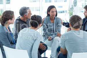 Concerned men comforting another in rehab group