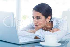 Tired businesswoman looking at her laptop
