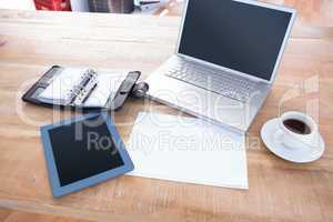 Diary with laptop and tablet on a desk