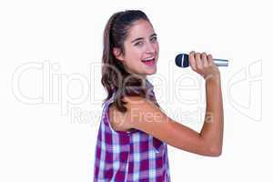 Happy pretty brunette singing on microphone