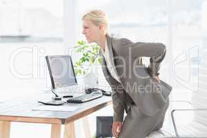Sad businesswoman having back pain