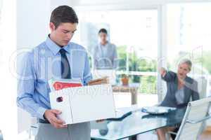 Businessman carrying his belongings in box