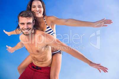 Man giving piggy back to his girlfriend at the beach