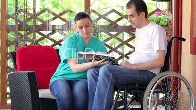 Physical therapist explaining exercises to young man in wheelchair