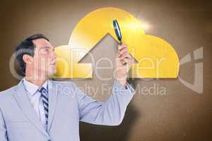Composite image of concentrated businessman using magnifying gla