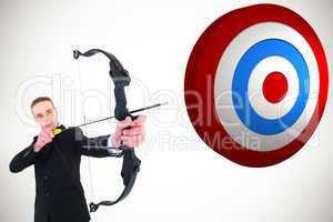 Composite image of concentrated businessman shooting a bow and a