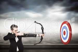 Composite image of elegant businessman shooting bow and arrow