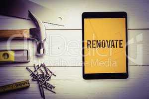 Renovate  against tablet displaying blueprint