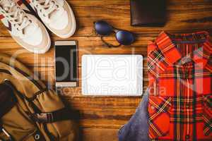 Shirt shoes jean glasses next to wallet smartphone and bag