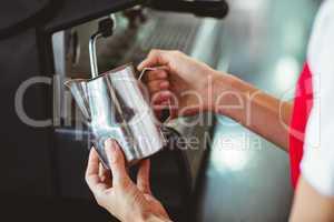 A barista using the coffee machine