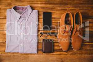 Shirt shoes glasses next to wallet and smartphone
