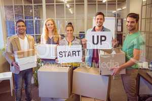 Creative business team holding cardboard written start up