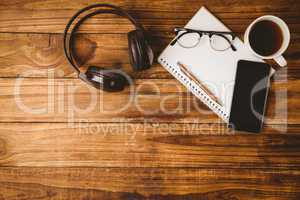 Pen glasses on the smartphone on notepad next to cup of coffee a