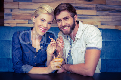 Cute couple on a date sharing a glass of orange juice
