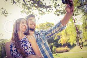 Cute couple doing selfie with retro camera in the park