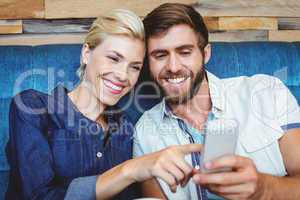 Cute couple on a date watching photos on a smartphone