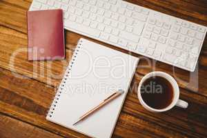 Pen on notepad next to cup of coffee passport and keyboard
