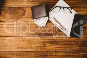 Pen and glasses on notepad next to wallet and smartphone