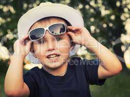 Portrait of a cheerful little boy in sunglasses