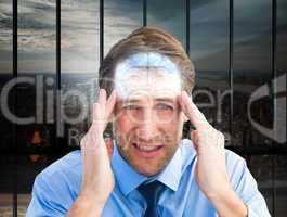 Composite image of young businessman with severe headache
